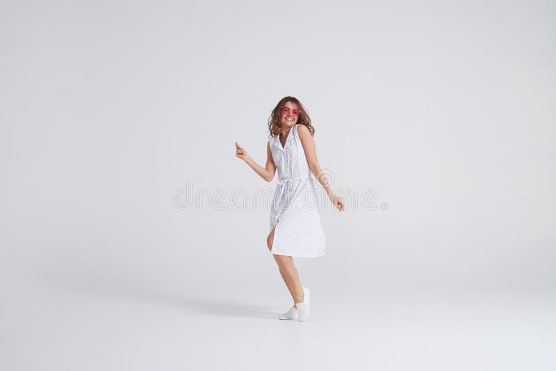 Attraktiv flicka i klänningdans i studio på vit bakgrund arkivfoton