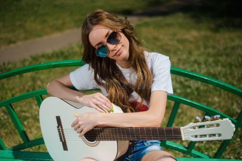 Attraktiv flicka i solglasögon som sitter med en gitarr royaltyfri foto