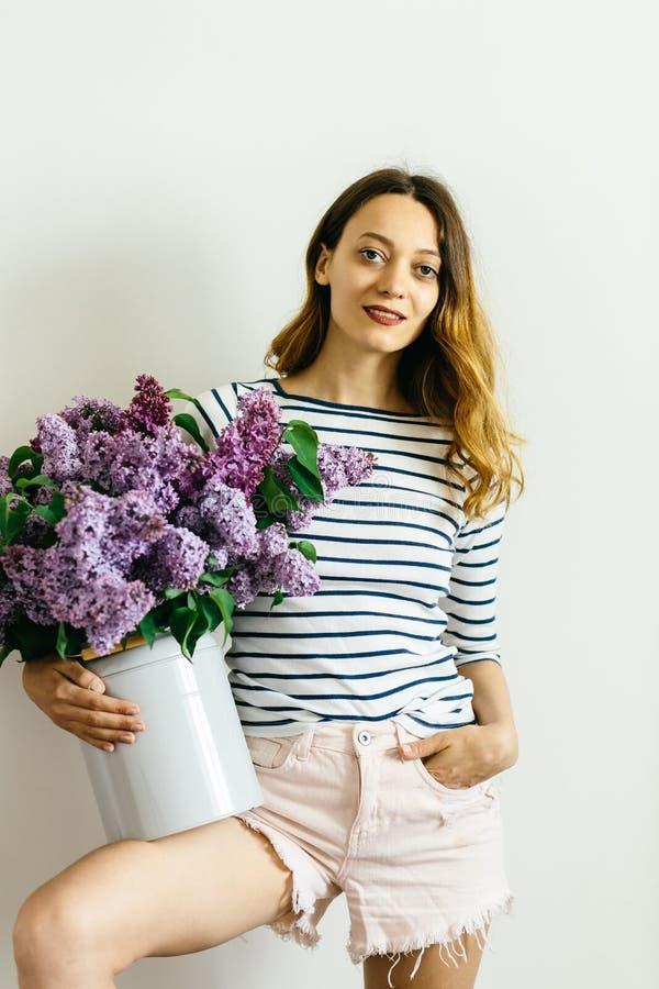Attraktiv flicka med en violett bukett av lilan på en vit bakgrund royaltyfria foton
