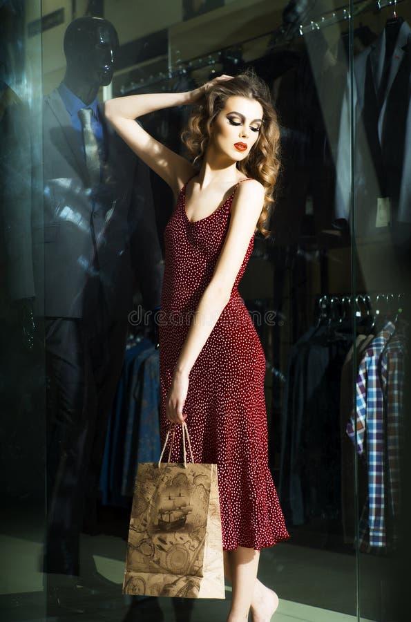 Attraktiv flicka nära shoppingfönster arkivbild