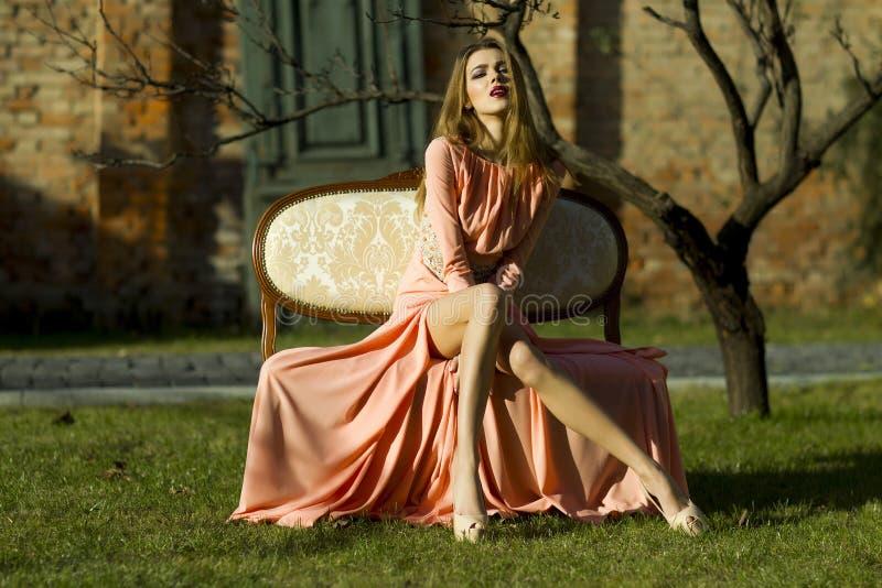 Attraktiv flicka på den utomhus- soffan royaltyfri foto