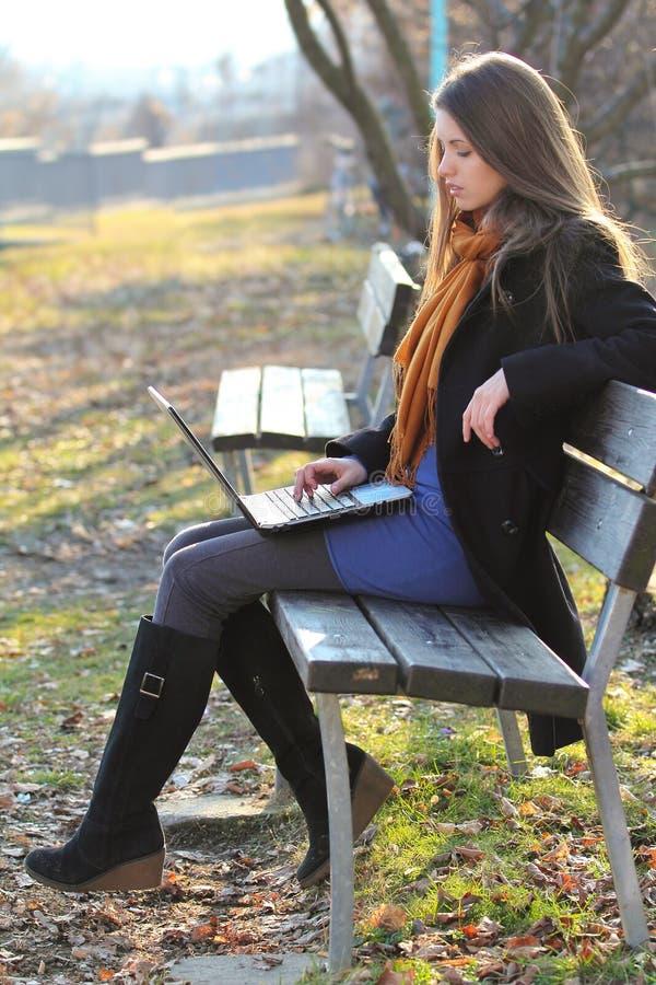 Attraktiv flicka som använder en bärbar datordator som placeras på en ta av planet fotografering för bildbyråer