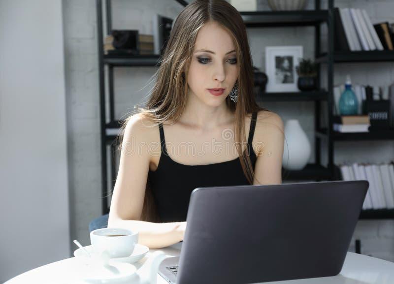 Attraktiv flicka som inomhus arbetar på en bärbar dator royaltyfri foto