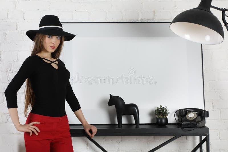 Attraktiv flicka som inomhus poserar i svart hatt arkivbilder