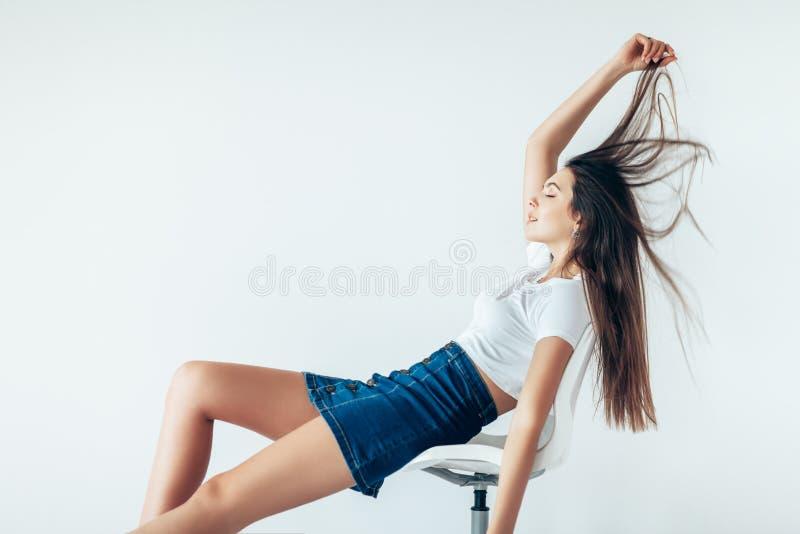 Attraktiv flicka som ligger på stol som spelar hår som är lyckligt royaltyfria foton