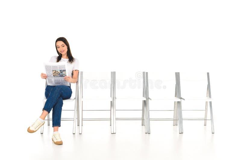attraktiv flicka som sitter på stol med korsade ben och läser den isolerade tidningen royaltyfri fotografi