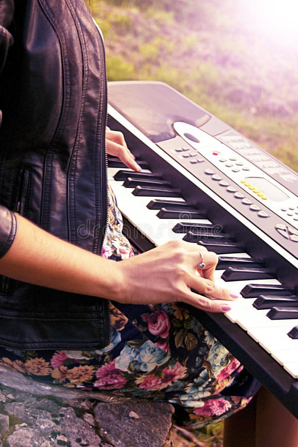 Attraktiv flicka som spelar en synt på naturen Ett elektriskt piano står i natur arkivfoto