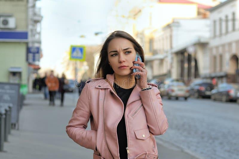 Attraktiv flicka som talar på telefonen, medan gå på sidewaen royaltyfria foton