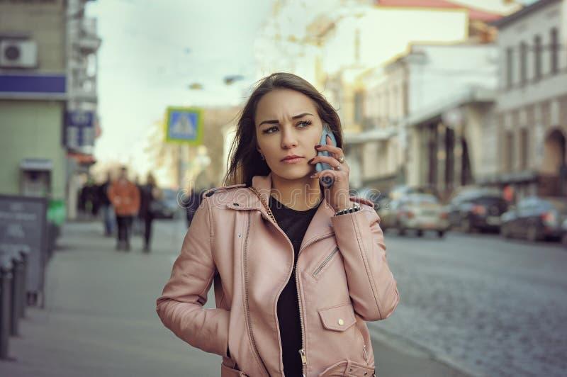 Attraktiv flicka som talar på telefonen, medan gå på sidewaen arkivfoton