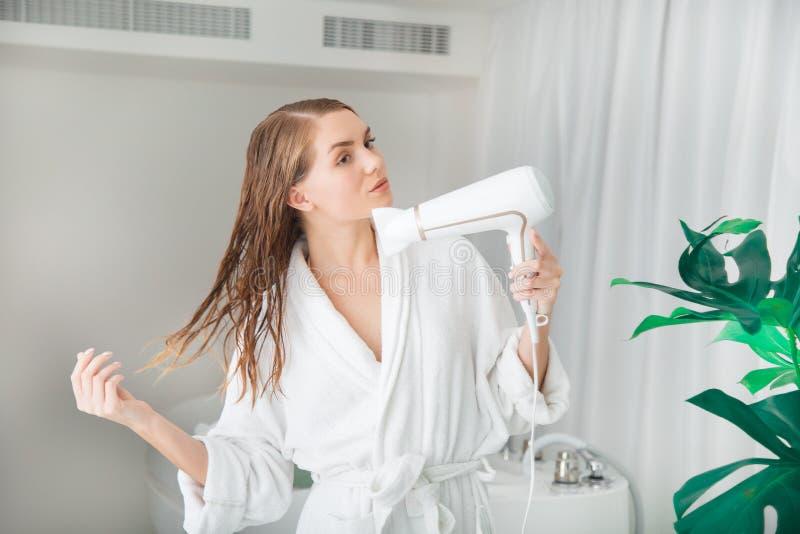 Attraktiv flicka som torkar hennes våta hår vid hårtork arkivbild