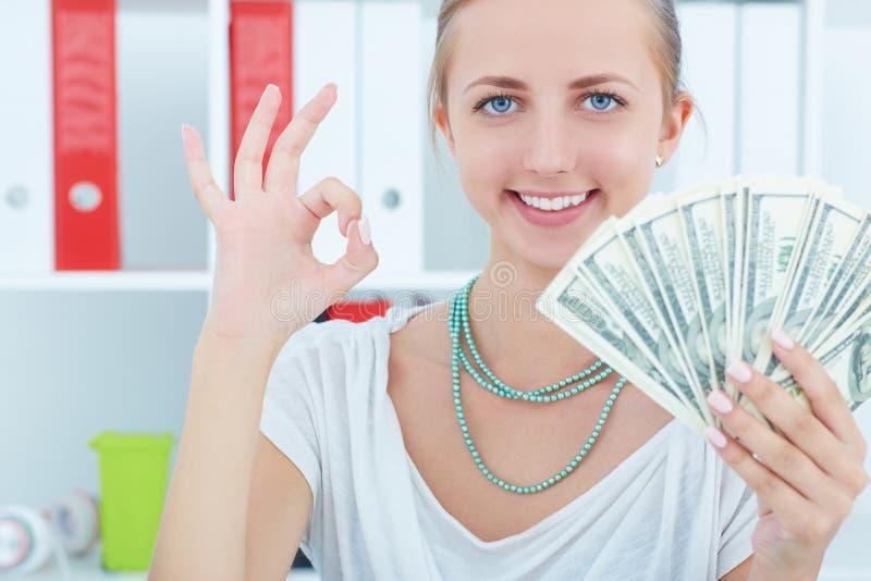 Attraktiv gladlynt kvinnlig som visar många sedlar av hundra dollar Vinnande pengarprisconce arkivbild