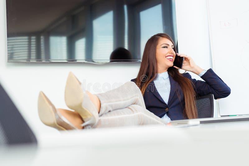 Attraktiv gladlynt modell i formella kläder genom att använda smartphonen royaltyfri bild