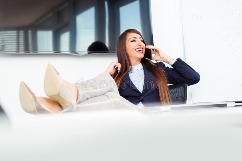 Attraktiv gladlynt modell i formella kläder genom att använda smartphonen royaltyfria bilder