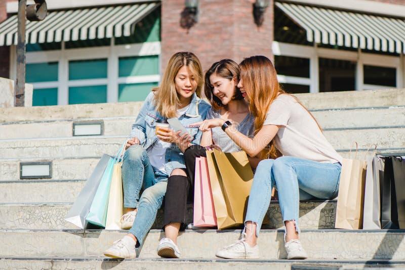 Attraktiv härlig asiatisk kvinna som använder en smartphone, medan shoppa i staden Lyckligt ungt asiatiskt tonårs- på den stads-  royaltyfri bild