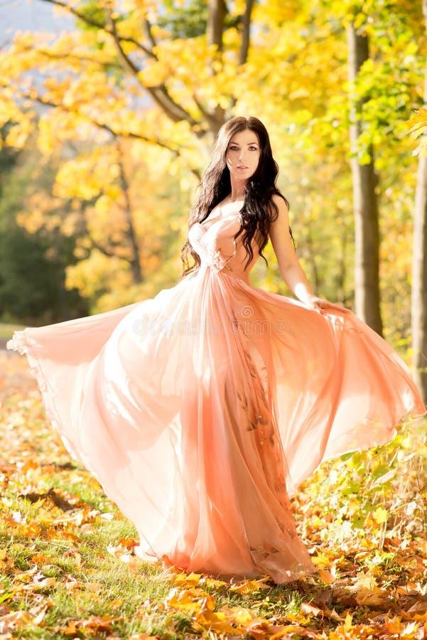 attraktiv härlig kvinna Natur höst, gula blad för nedgång Orange klänning för mode arkivfoto