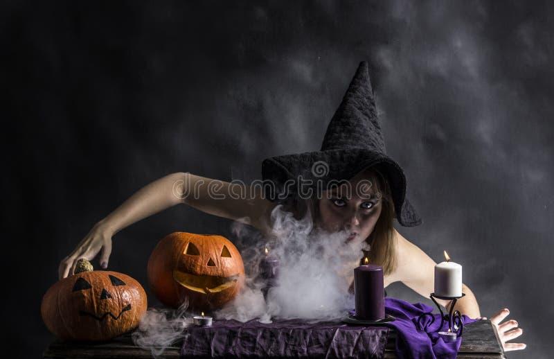 Attraktiv häxa i den wizarding lya med rök som går från hennes mun royaltyfria bilder