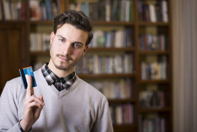 Attraktiv hållande kreditkort för ung man som ser kameran royaltyfri foto