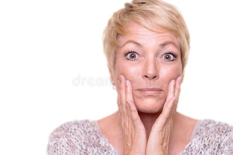 Attraktiv hög blond kvinna som kontrollerar hennes hy arkivfoto