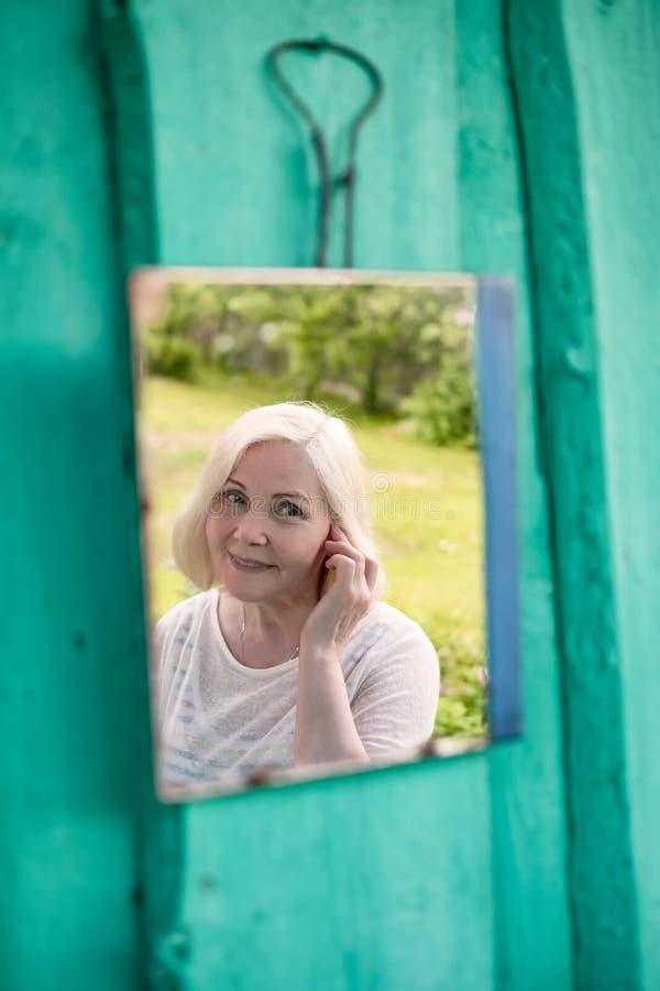 Attraktiv hög blond kvinna som ser henne i spegel arkivfoton