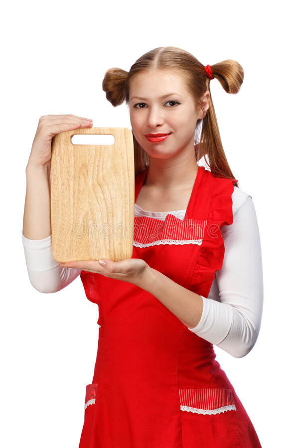 Attraktiv hemmafru i rött förkläde med roliga hästsvansar och woode royaltyfri fotografi