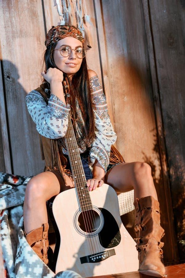 Attraktiv hippieflicka i huvudbindeln och exponeringsglas som poserar med en gitarr royaltyfria bilder
