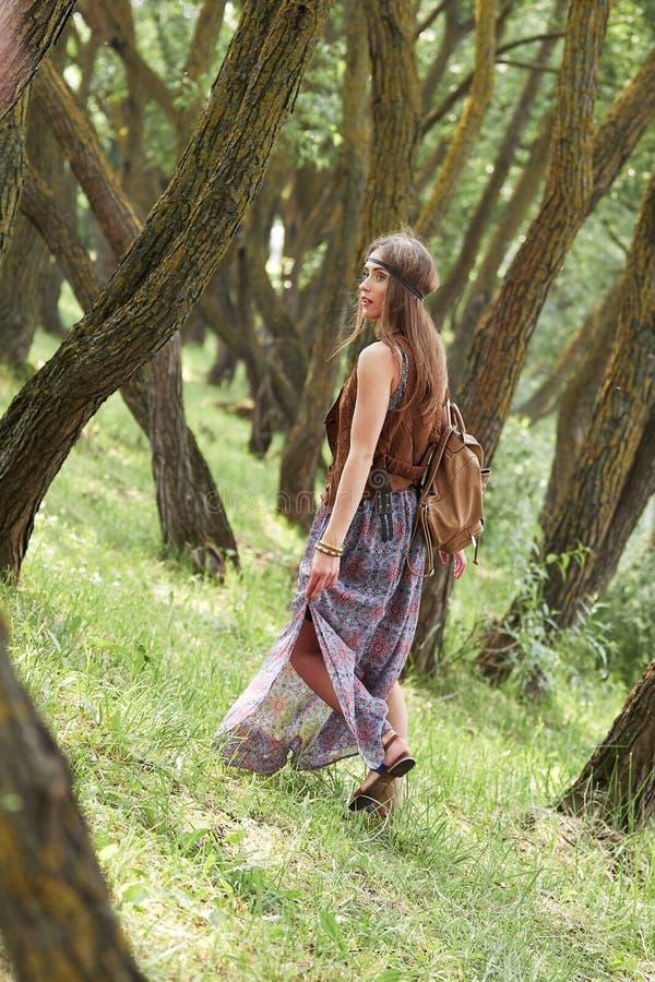Attraktiv hippieflicka som går bland träden i skogen royaltyfri foto