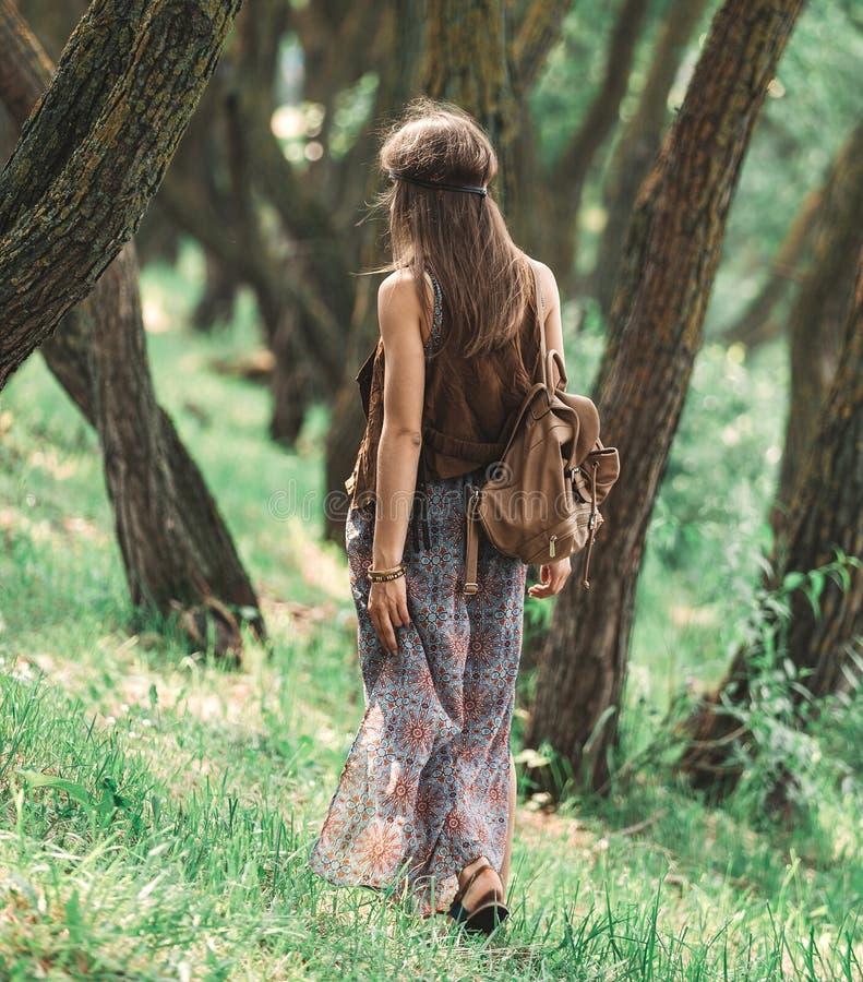 Attraktiv hippieflicka som g?r bland tr?den i skogen royaltyfri bild