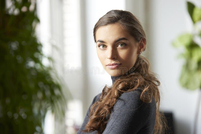 Attraktiv inomhus stående för ung kvinna royaltyfri bild