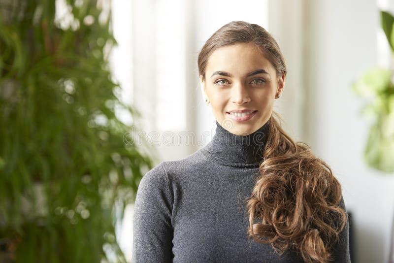 Attraktiv inomhus stående för ung kvinna arkivfoto