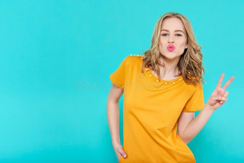 Attraktiv kall ung kvinna som blåser en kyss och gör gest för hand för fredtecken arkivfoton