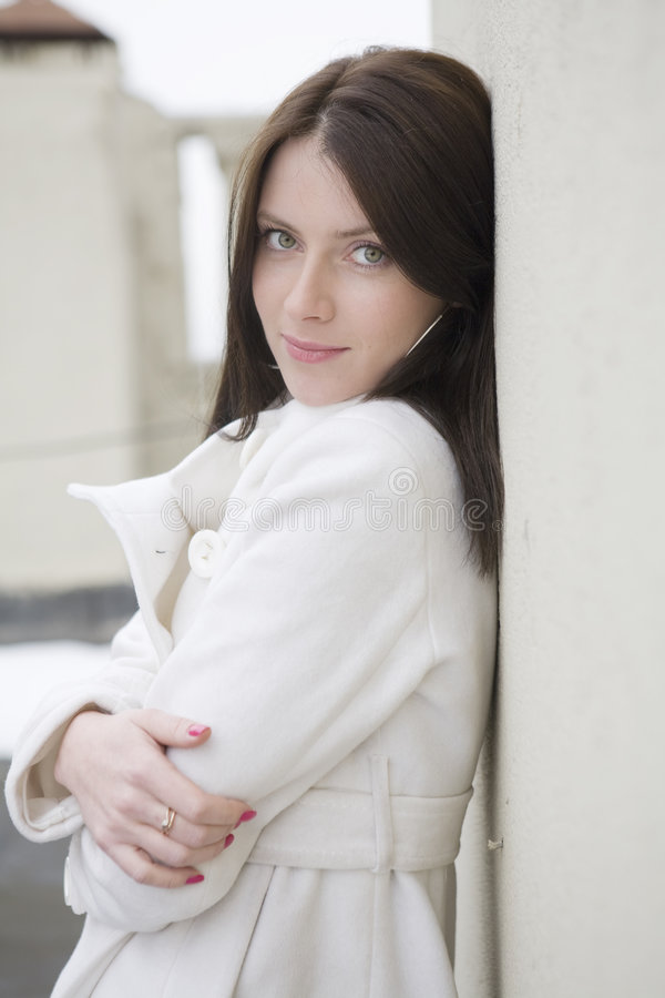 attraktiv kvinna för överrockväggwhite royaltyfria foton