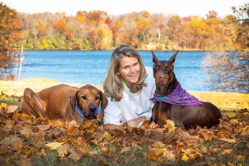 Attraktiv kvinna för mellersta ålder som kopplar av på sjön med hennes 2 stora älsklings- hundkapplöpning arkivbild