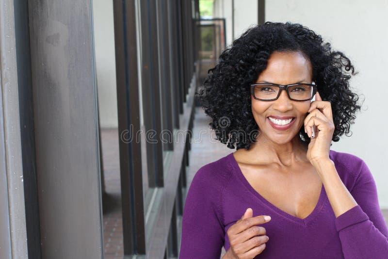 Attraktiv kvinna för mogen affär med den smarta telefonen i staden royaltyfria foton