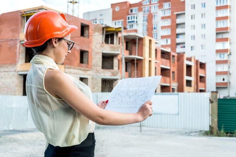 Attraktiv kvinna i byggmästarehjälmen som ser ritningen arkivbild