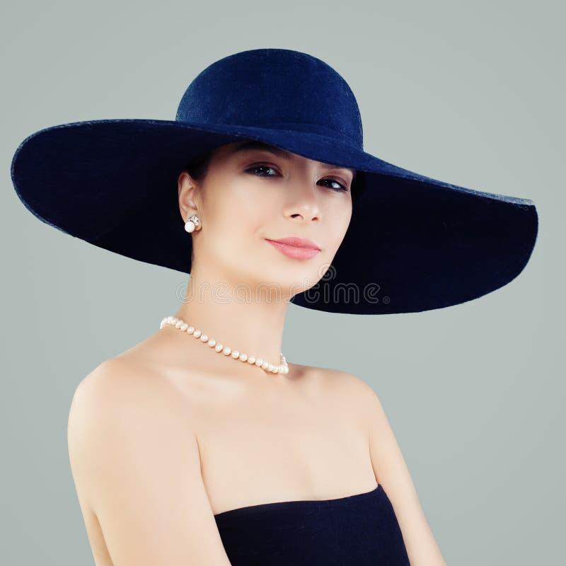 Attraktiv kvinna i den blåa klassiska hatten och vita pärlor, modestående royaltyfria foton