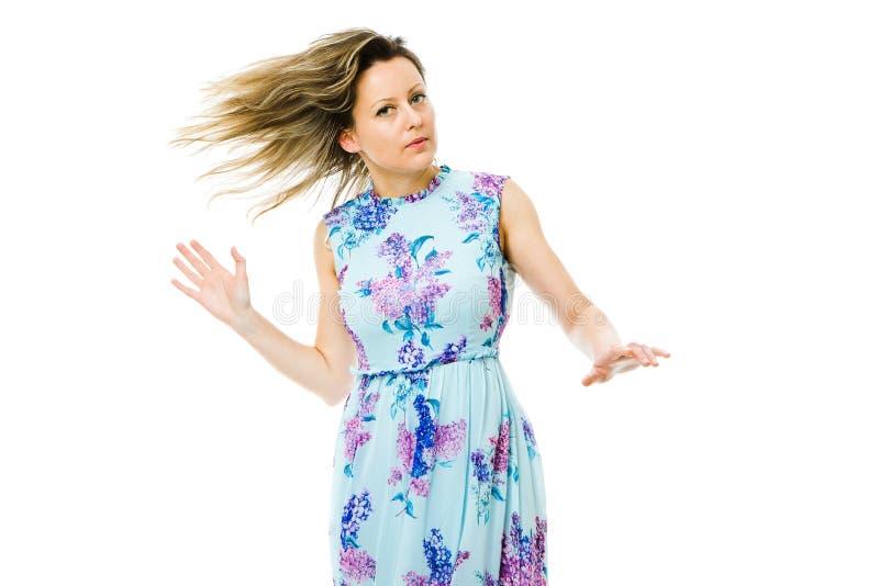 Attraktiv kvinna i den blommiga kl?nningen som poserar p? vit bakgrund royaltyfria bilder
