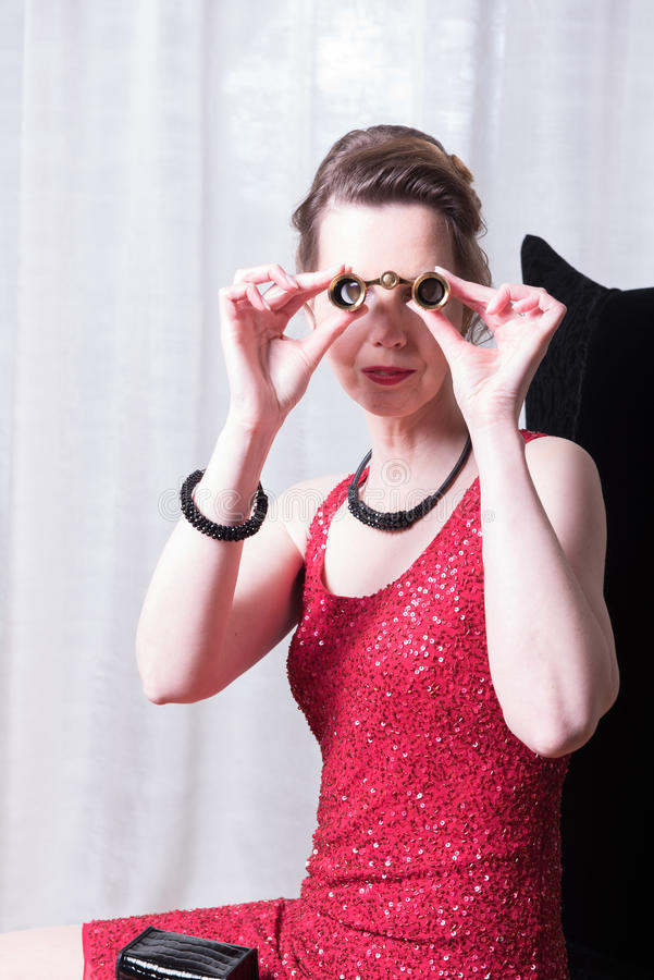 Attraktiv kvinna i den röda klänningen som ser hoförstoringsglaset arkivfoton