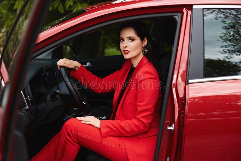 Attraktiv kvinna i den röda smarta dräkten som sitter i bil arkivbild