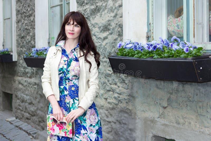 Attraktiv kvinna i klänning med härliga blommor i gammal stad fotografering för bildbyråer