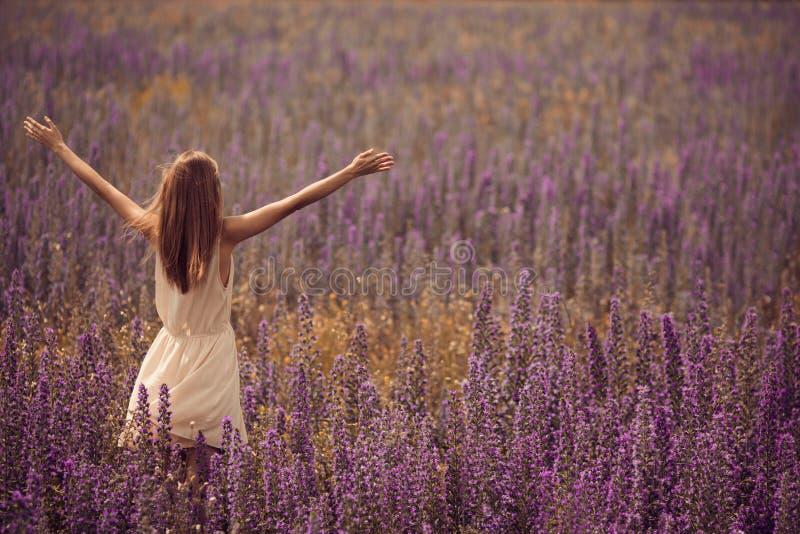 attraktiv kvinna i klänning på blommafältet arkivbilder