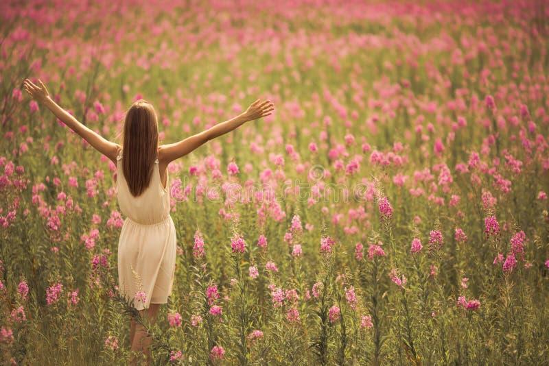 attraktiv kvinna i klänning på blommafältet arkivfoto