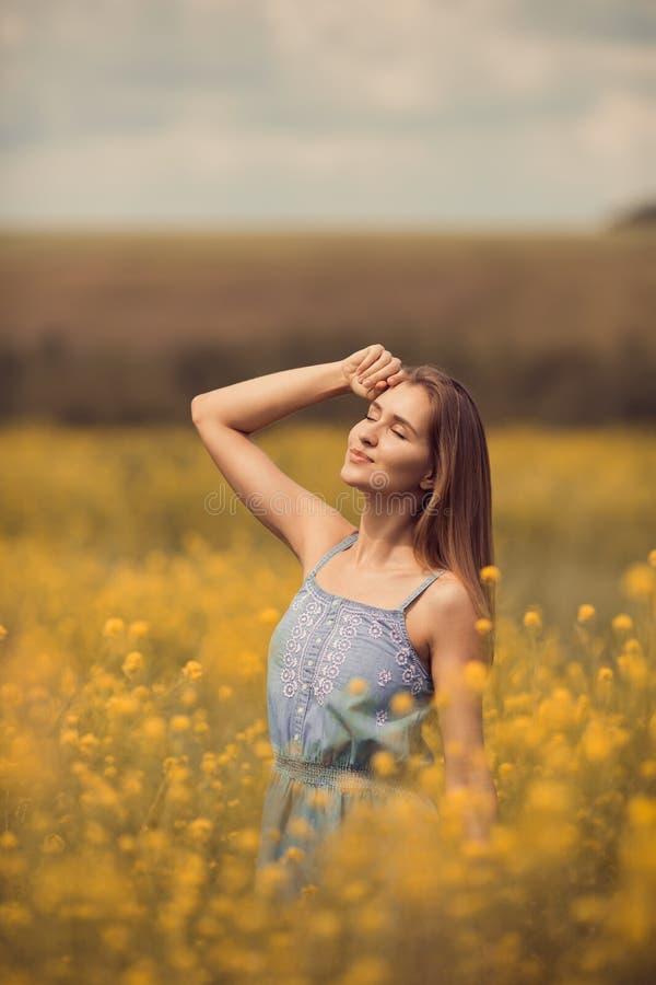 attraktiv kvinna i klänning på blommafältet arkivfoton