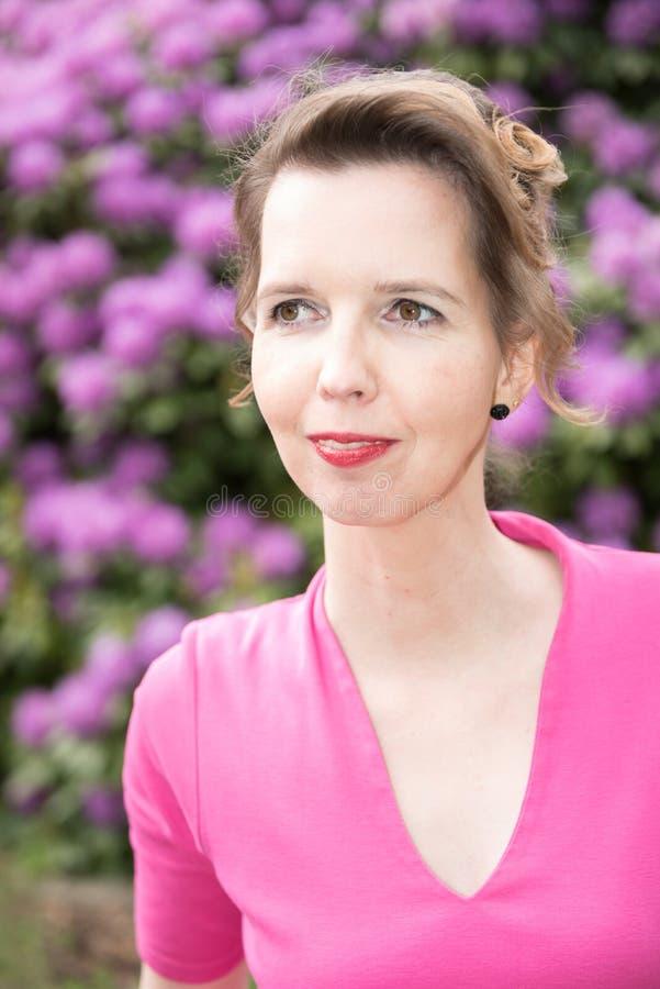 Attraktiv kvinna i lilor i trädgården royaltyfria foton