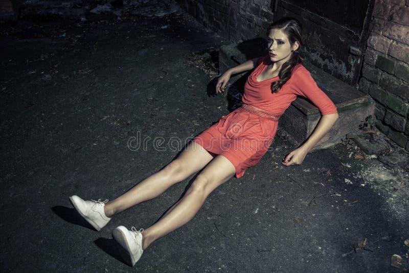 Attraktiv kvinna i ljust klänningsammanträde på vägen och benägenhet på arkivfoton