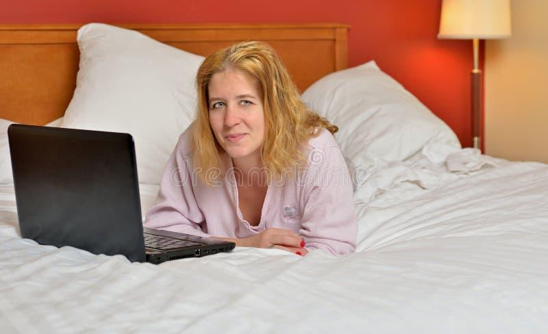 Attraktiv kvinna i pajamas i säng med bärbar datordatoren royaltyfri fotografi