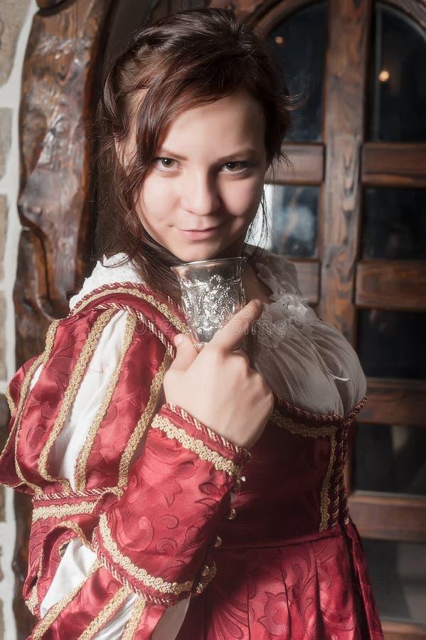 Attraktiv kvinna i röd klänning i retro barock royaltyfri bild