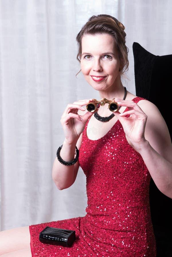 Attraktiv kvinna i röd klänning med förstoringsglaset arkivfoton