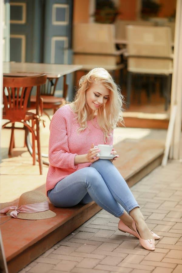 Attraktiv kvinna i romantiskt lynne som ler i lycka som sitter p? tabellen som b?r det rosa omslaget, stilfull dr?kt som v?ntar fotografering för bildbyråer