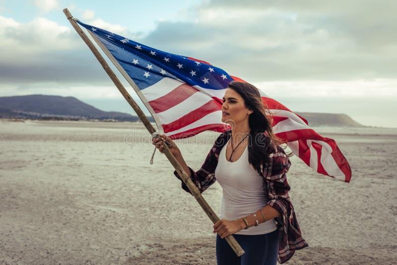 Attraktiv kvinna med amerikanska flaggan på stranden royaltyfria foton
