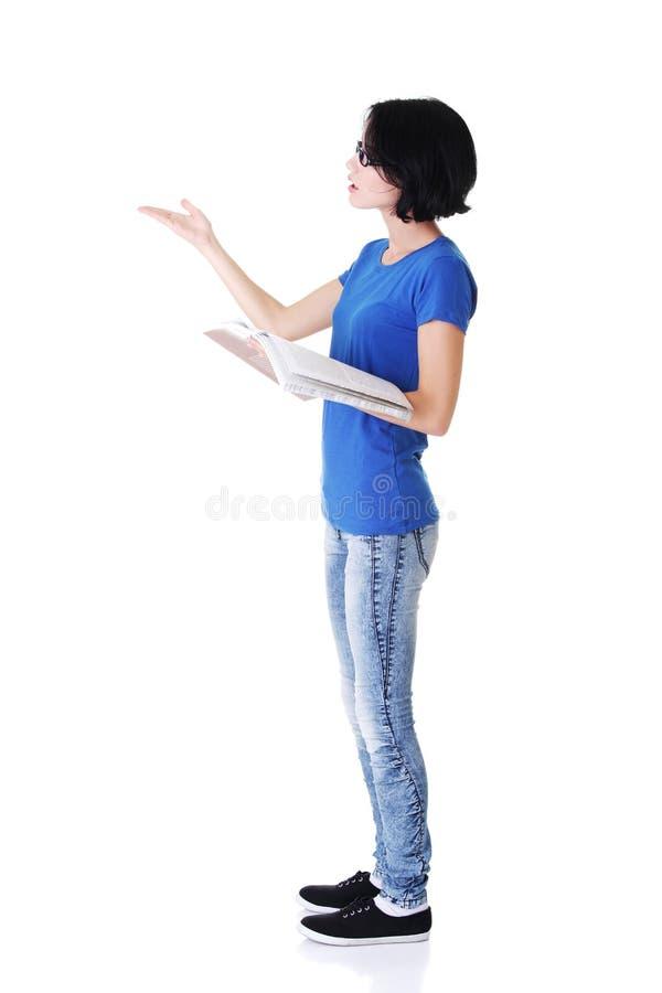 Attraktiv kvinna med arbetsboken. Sidosikt. Peka på kopieringsspac royaltyfria foton
